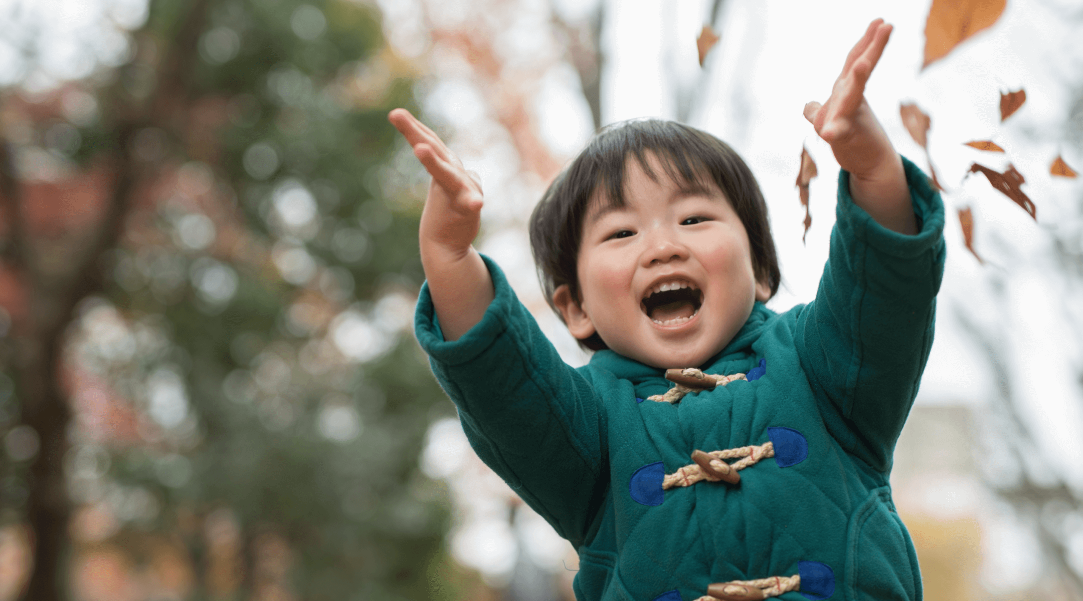 Young child throwing leaves