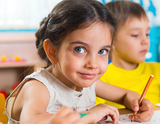 Young smiling girl drawing in a classroom