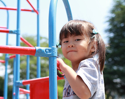 Young girl climbing on a jungle gym